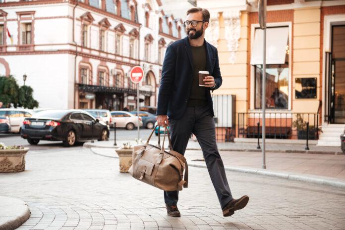 Młody, przystojny mężczyzna, idący ulicą z modną torbą